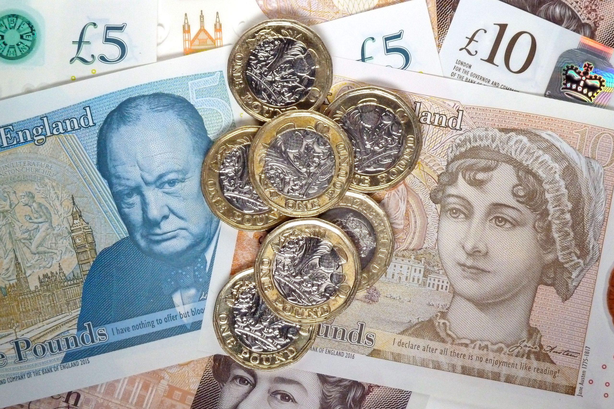 Gros plan sur les nouveaux billets de 5 et 10 livres sterling et sur la pièce de monnaie britannique.