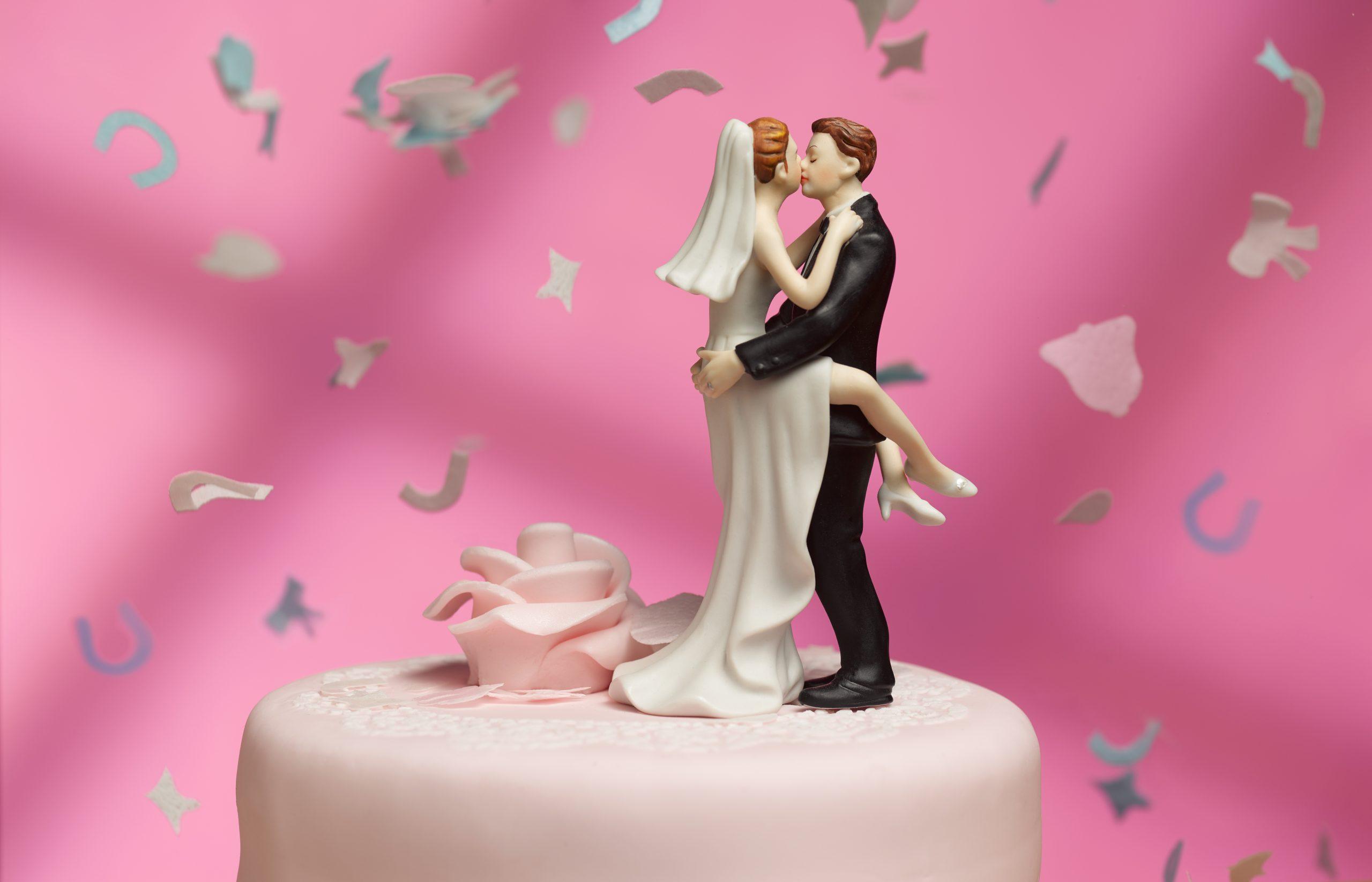 Un gâteau de mariée et de marié entouré de confettis.