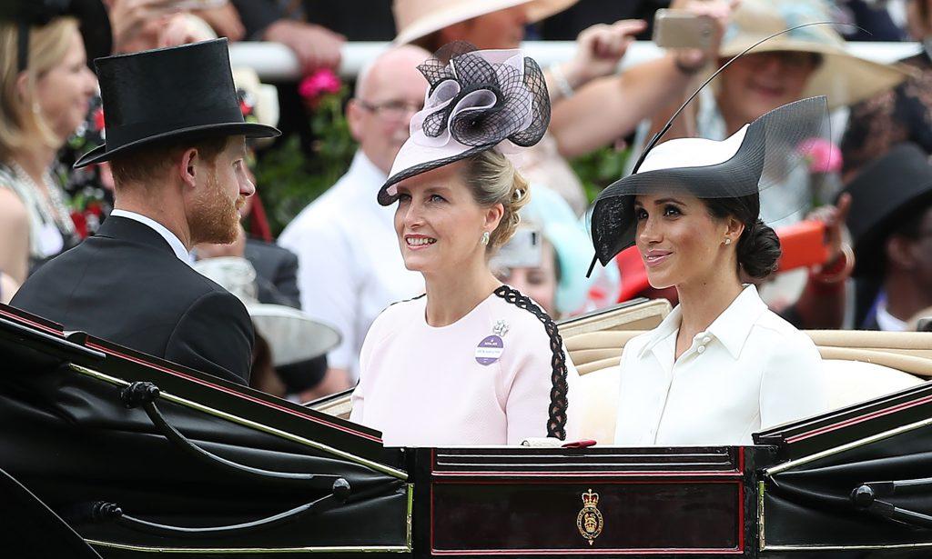 Le prince Harry, duc de Sussex, (à gauche) et son épouse la Britannique Meghan, duchesse de Sussex (à droite) arrivent avec la Britannique Sophie, comtesse de Wessex, lors de la première journée de la rencontre hippique Royal Ascot, à Ascot, à l'ouest de Londres, le 19 juin 2018.