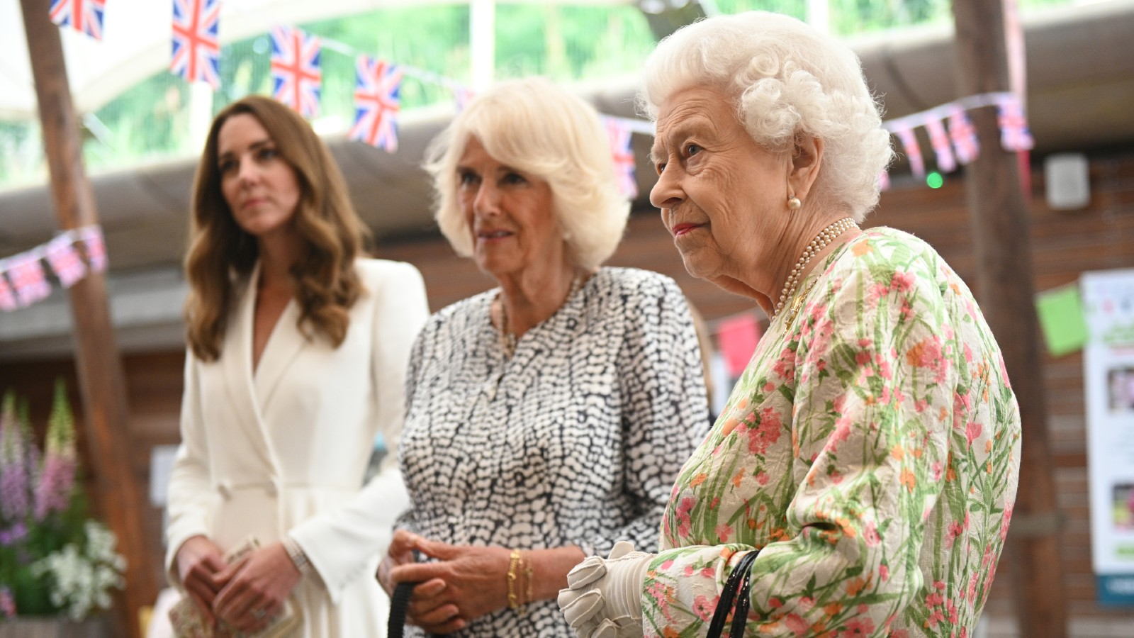 Catherine, duchesse de Cambridge (G), Camilla, duchesse de Cornouailles (C) et la reine Elizabeth II rencontrent des personnes issues de communautés de Cornouailles lors d'un événement organisé pour célébrer l'initiative The Big Lunch à l'Eden Project pendant le sommet du G7, le 11 juin 2021.