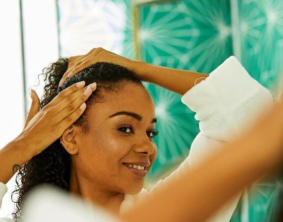 femme aux cheveux naturellement bouclés en peignoir de bain