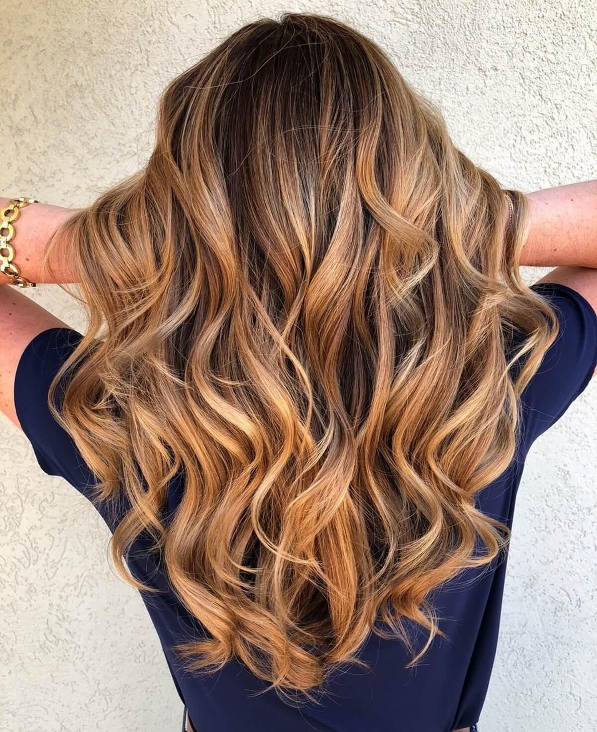 Cheveux bruns foncés avec des reflets auburn et caramel.