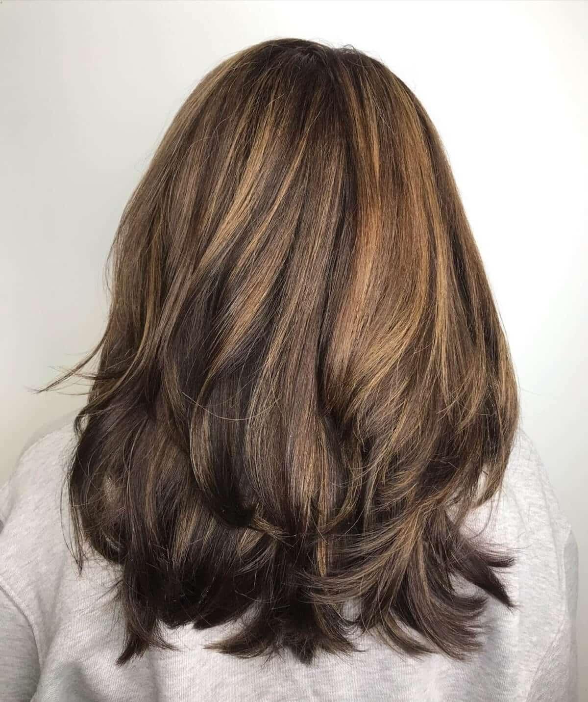 cheveux bruns foncés mi-longs avec des reflets caramel