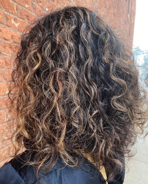 cheveux bouclés brun foncé avec des reflets caramel