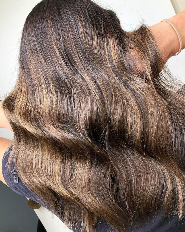cheveux marron foncé avec des mèches caramel clair sur cheveux mi-longs