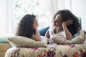 Une femme parle à sa fille de ses règles à la maison, sur le canapé.