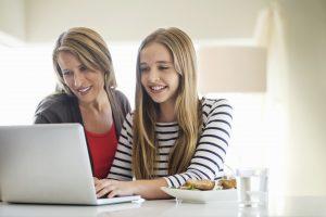 Mère et fille utilisant ensemble un ordinateur portable à la maison, après avoir appris comment parler des règles aux enfants.