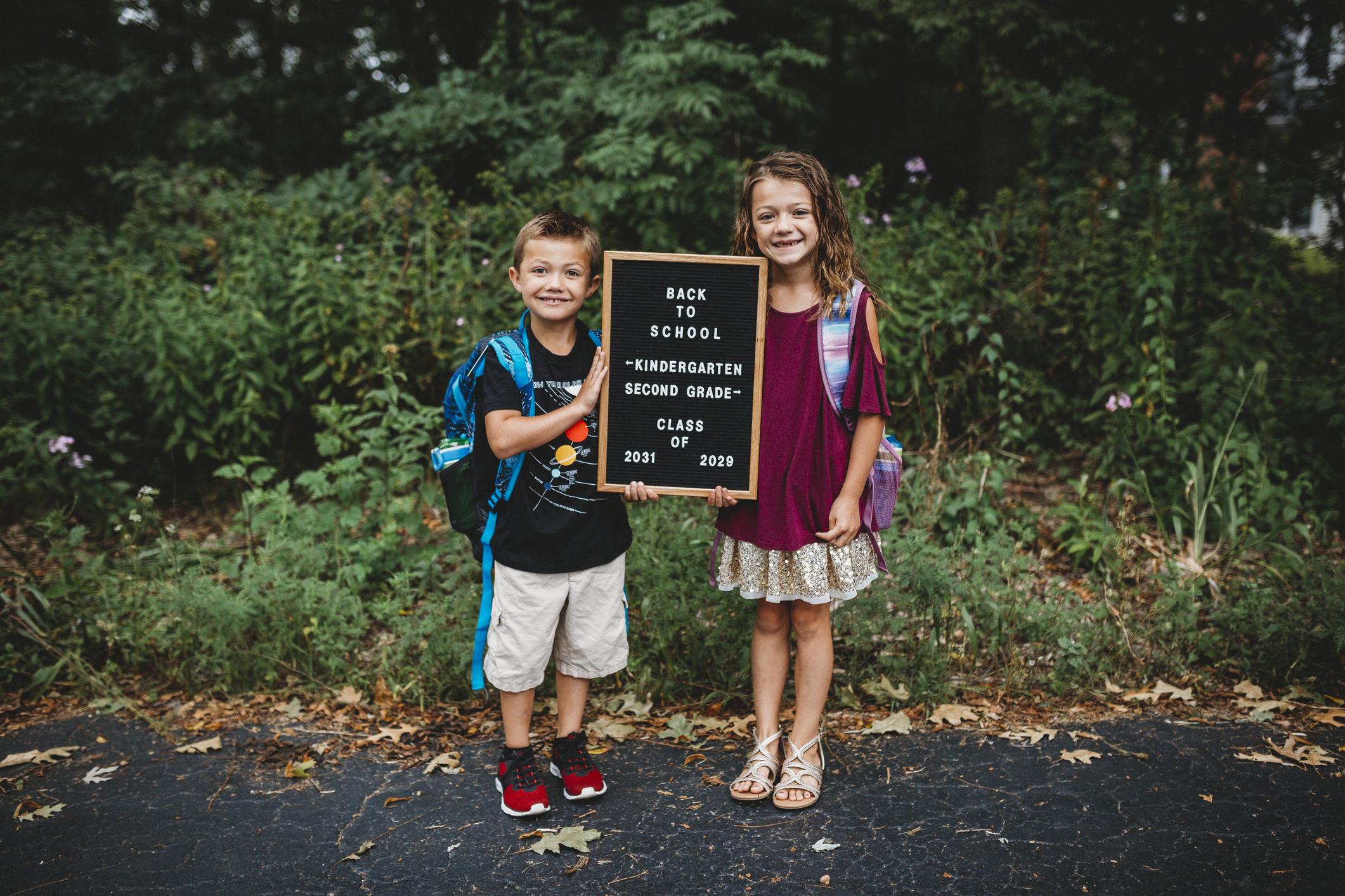 Deux frères et sœurs posant pour une photo de rentrée des classes.