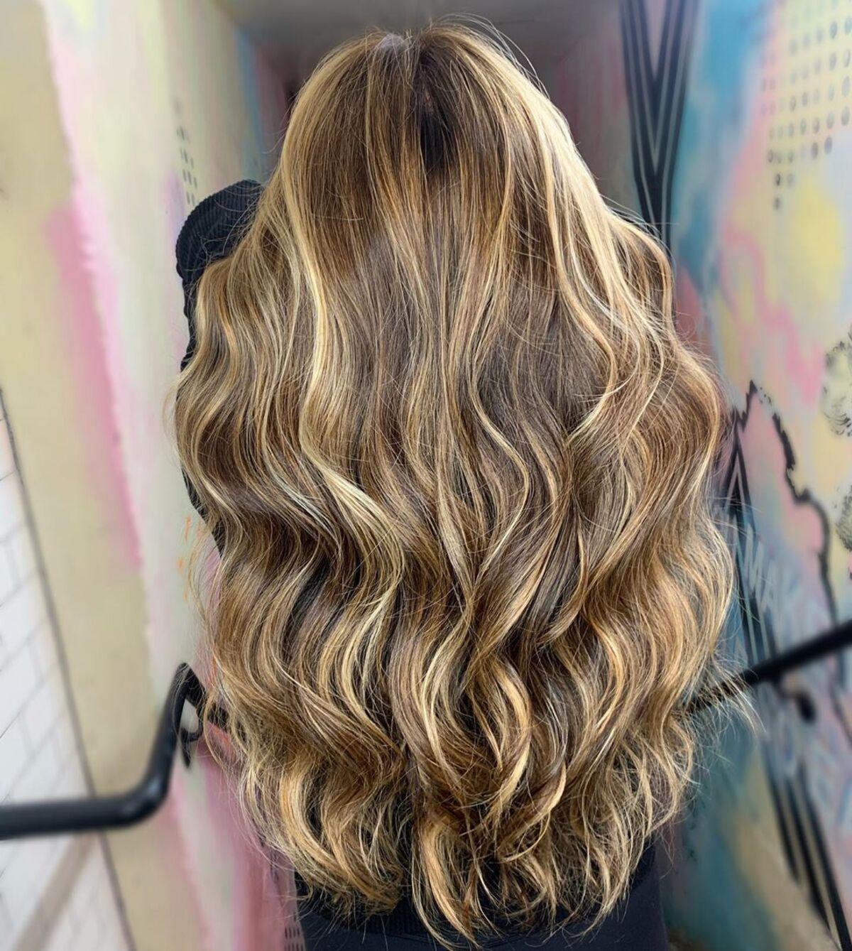 Mèches caramel et blondes sur cheveux châtain clair