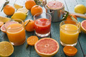 Trois verres de jus de fruits entourés de fruits coupés.