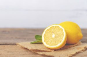 Citron coupé en deux avec un citron entier derrière.