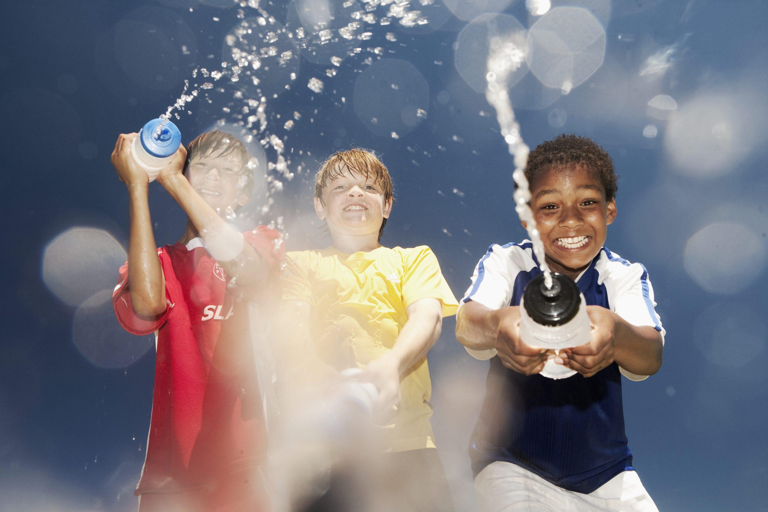 Une bataille d'eau entre enfants avec des vaporisateurs