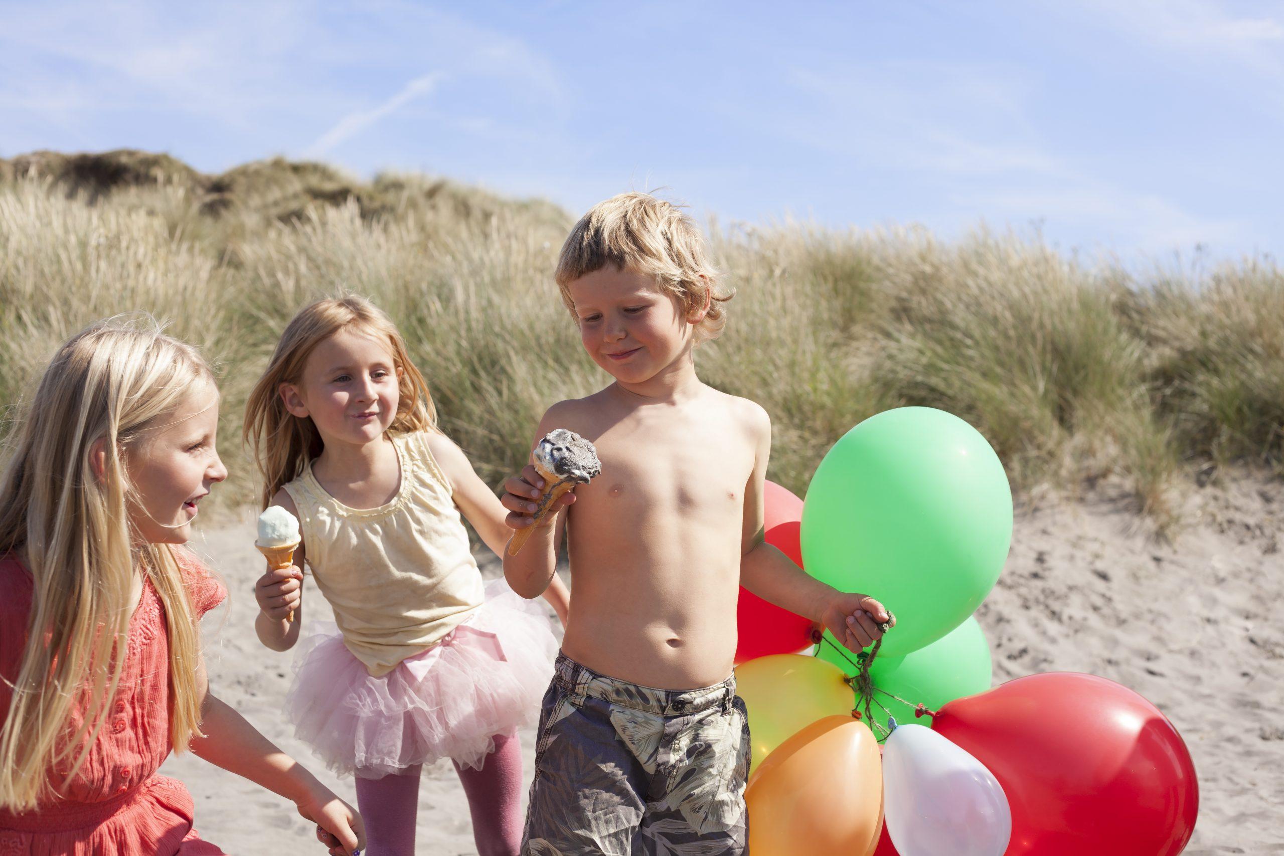 Enfants avec des ballons à la plage