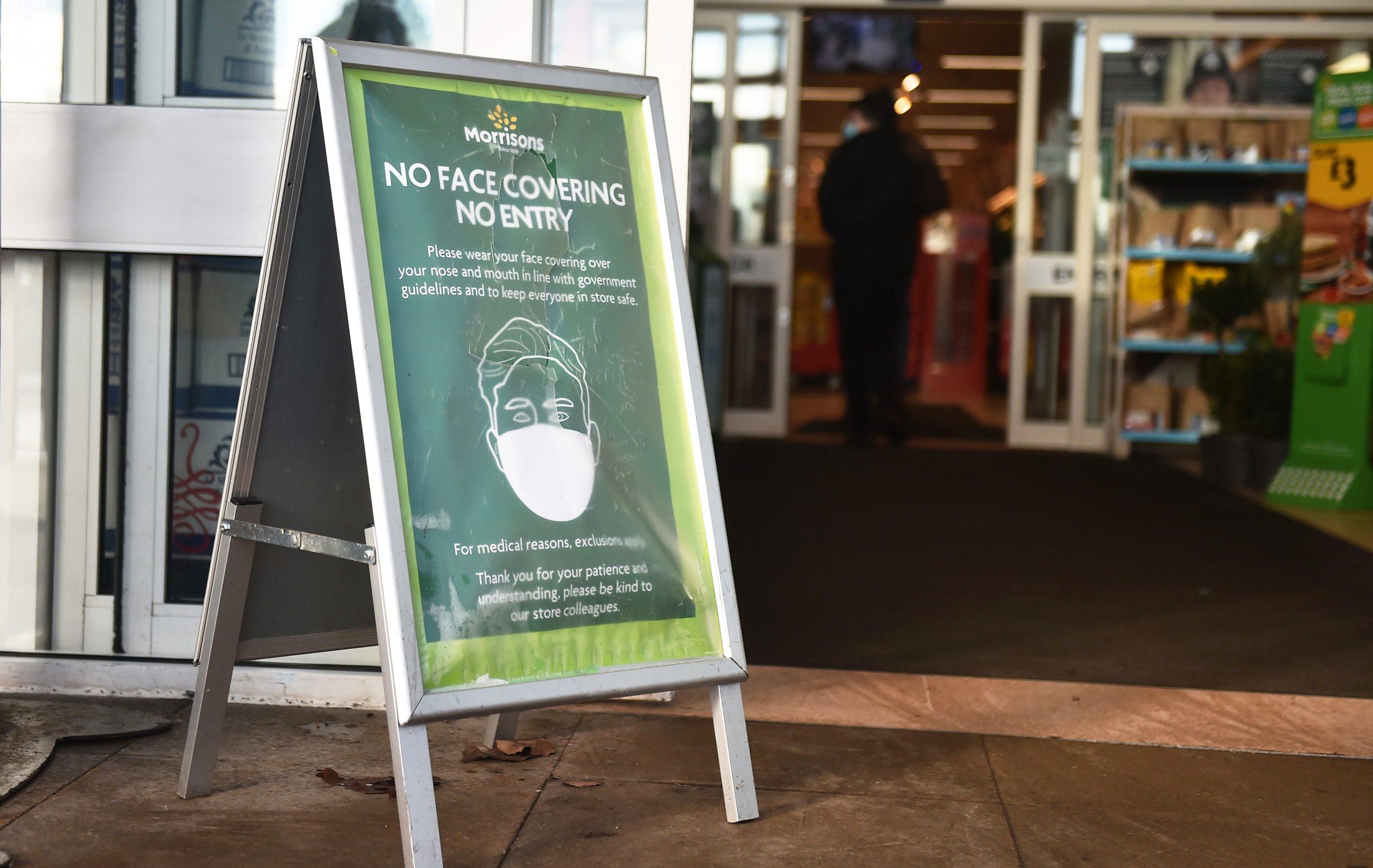 Un panneau indiquant le port d'un masque facial devant le supermarché Morrisons