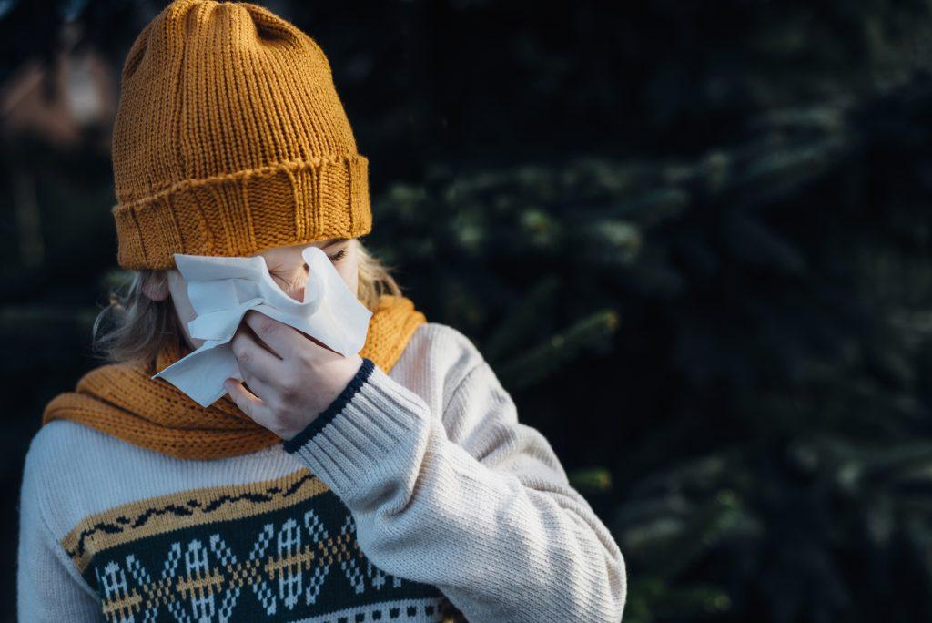 Un enfant se mouche avec un chapeau jaune en hiver.