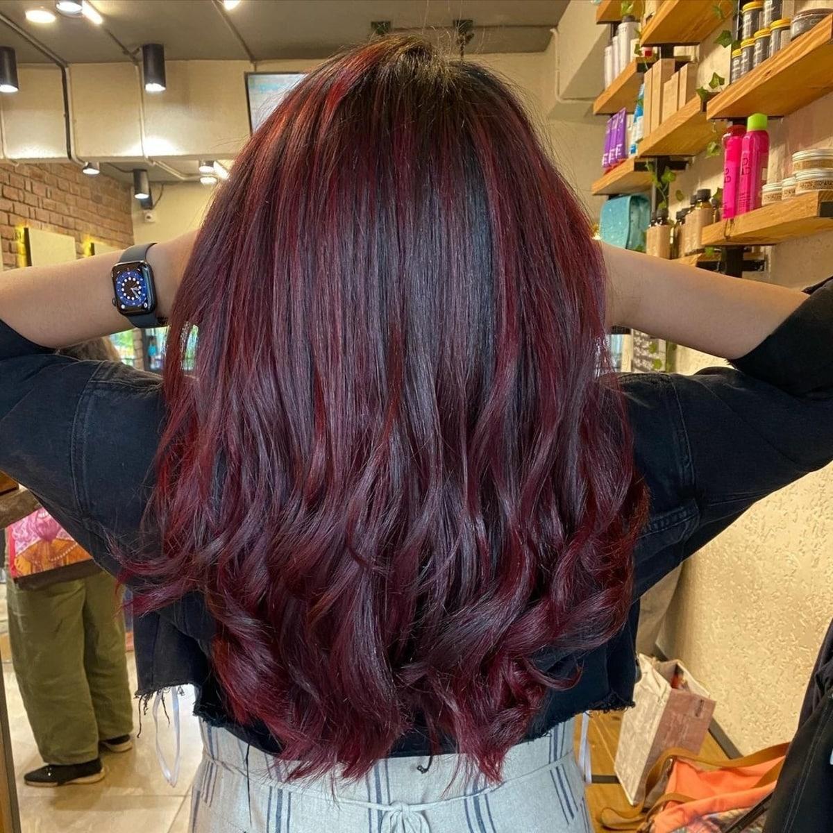 Mèches rouge vin pour une fille aux cheveux foncés