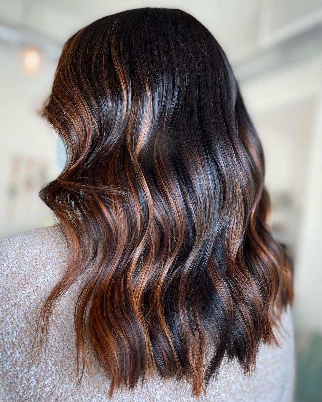 Mèches cuivrées sur une couleur de cheveux noire