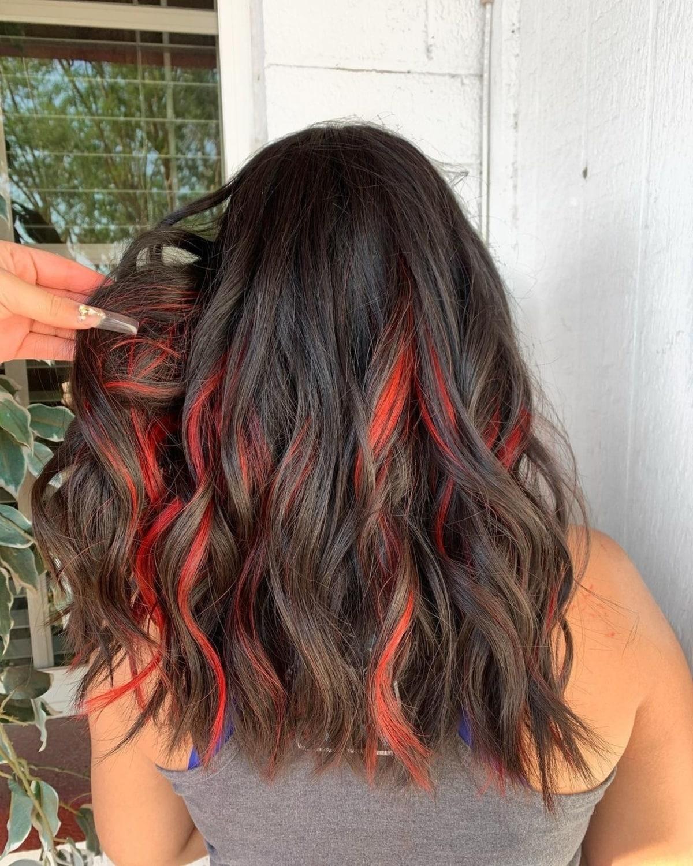 Cheveux noirs avec des reflets rouges en dessous