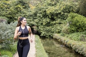 Femme courant le long de la rivière, essayant de perdre du poids de fermeture.