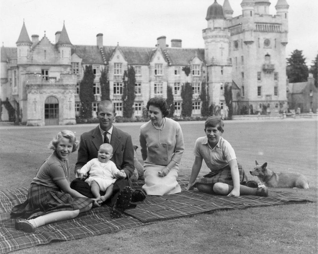 La reine Elizabeth II et le prince Philip, duc d'Édimbourg, avec leurs enfants, le prince Andrew (au centre), la princesse Anne (à gauche) et Charles, prince de Galles, assis sur un tapis de pique-nique devant le château de Balmoral, en Écosse.