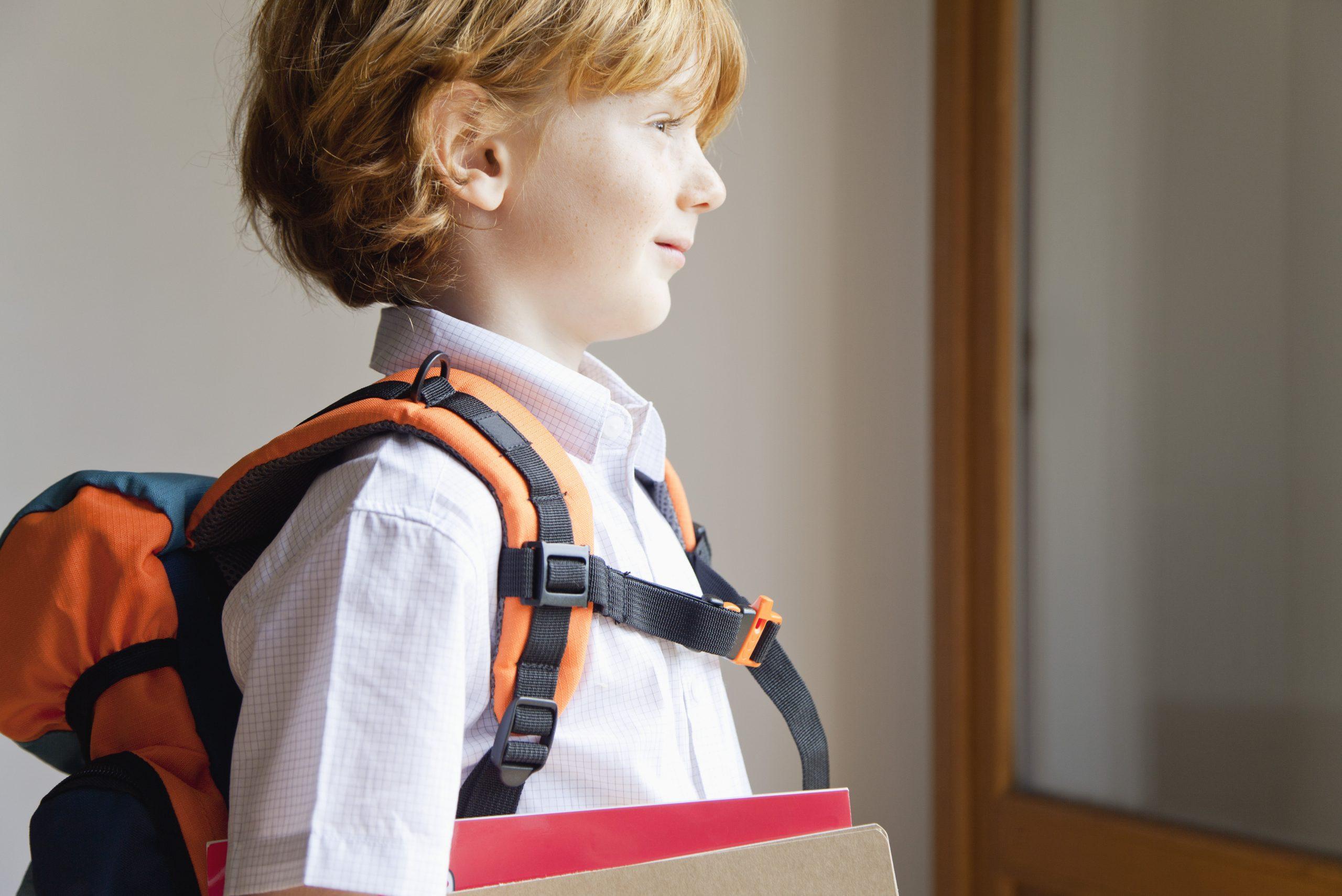 Un jeune garçon blond dans son uniforme, prêt pour son premier jour d'école.