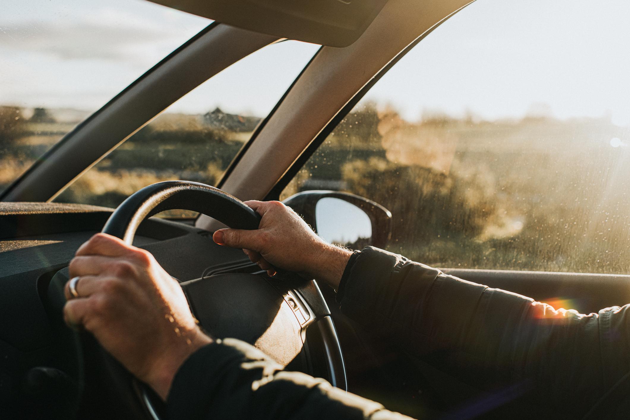 Les mains d'un parent sur le volant d'une voiture