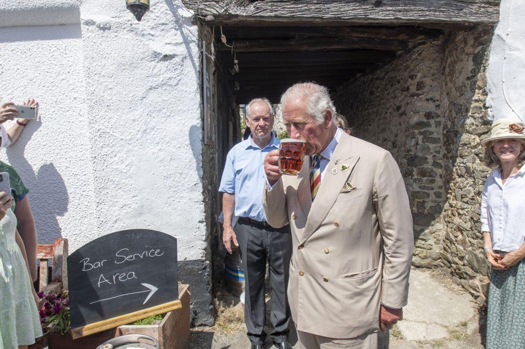 Le Prince Charles, Prince de Galles, boit une pinte de Bayes Topsail alors que lui et Camilla, Duchesse de Cornouailles (pas sur la photo) visitent le Duke of York Public House dans le Devon.