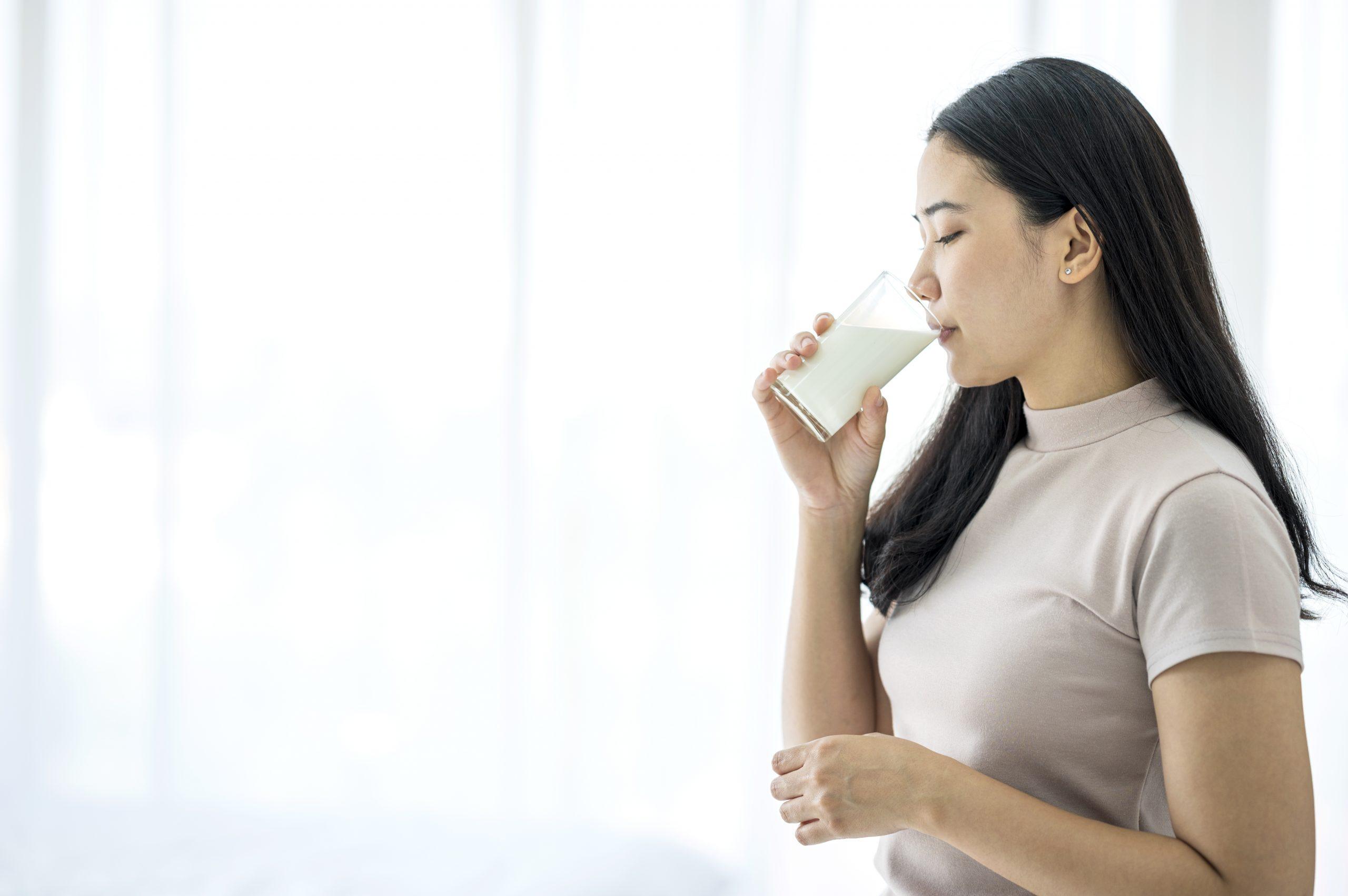 une femme buvant du lait d'avoine à la maison