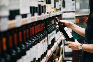 Bouteilles de vin rouge sur une étagère dans un magasin.