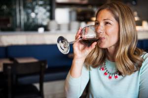 Femme buvant du vin rouge dans un verre