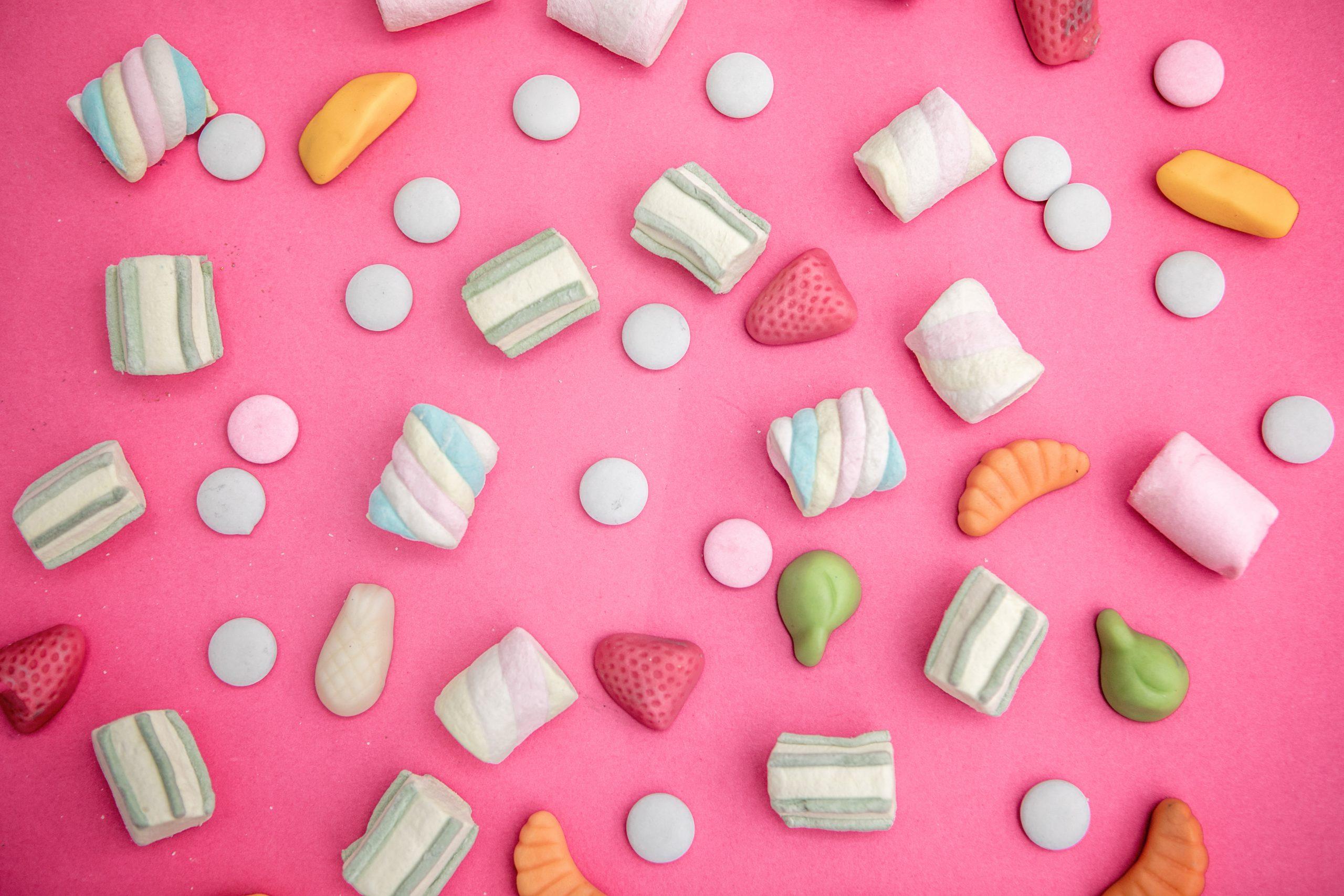 un assortiment de bonbons sur un fond rose