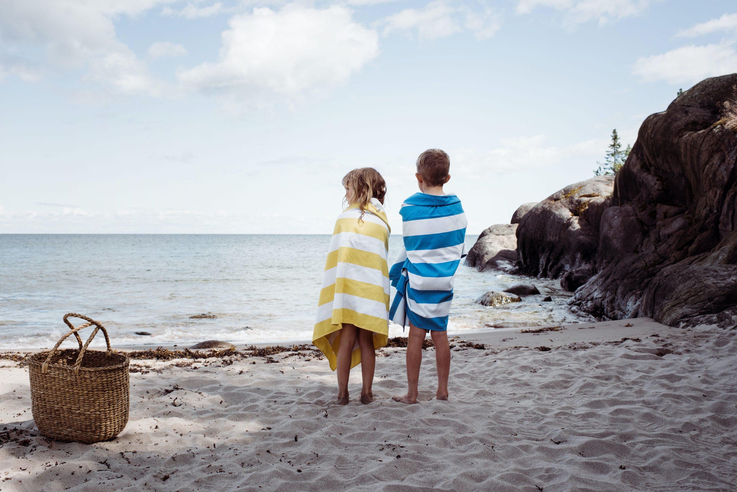 Deux jeunes enfants enveloppés dans des serviettes à la plage.