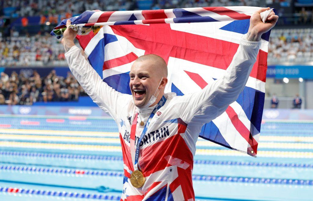 Adam Peaty, de l'équipe de Grande-Bretagne, pose avec le drapeau de son pays après avoir remporté l'or au 100 mètres brasse masculin lors de la troisième journée des Jeux olympiques de Tokyo 2020.