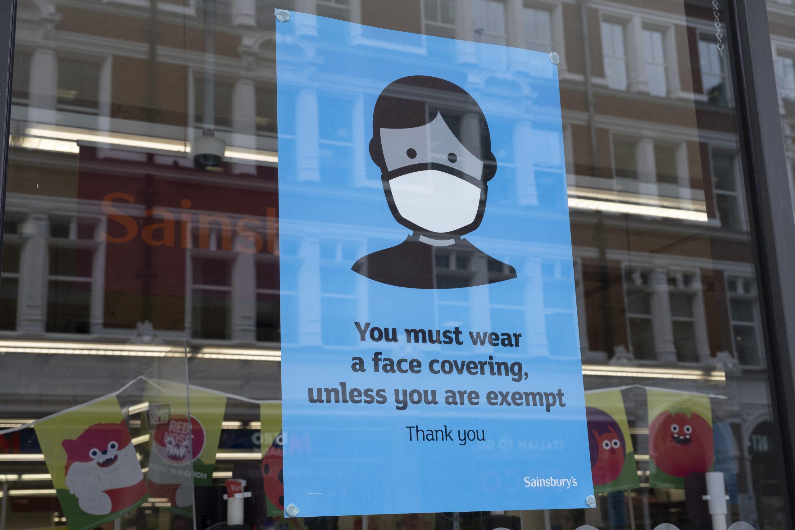 Un panneau indiquant le port d'un masque facial dans un supermarché Sainsbury's.