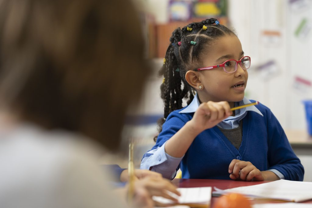 Jeune fille en uniforme scolaire tenant un crayon à l'école.