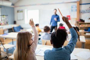 Vue arrière d'élèves de retour à l'école, assis les mains levées dans une salle de classe.