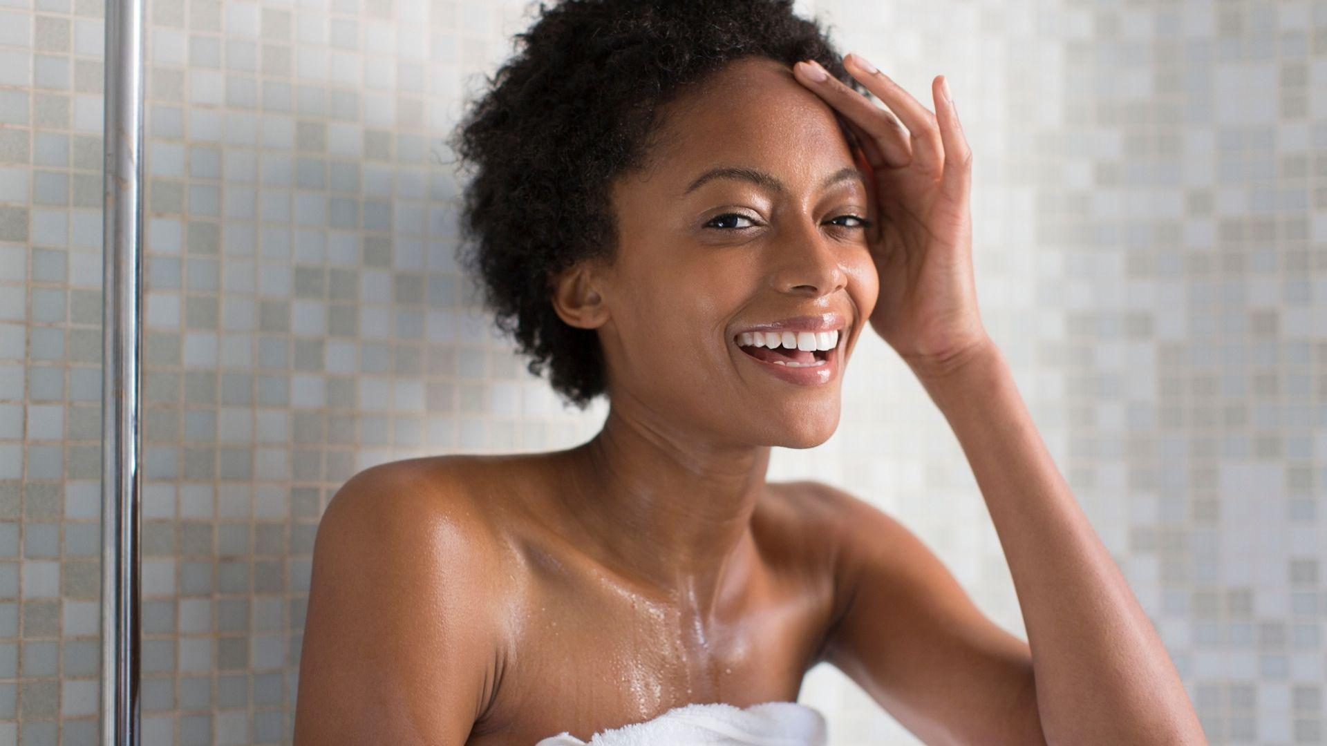 Femme avec des cheveux afro sous la douche, souriant