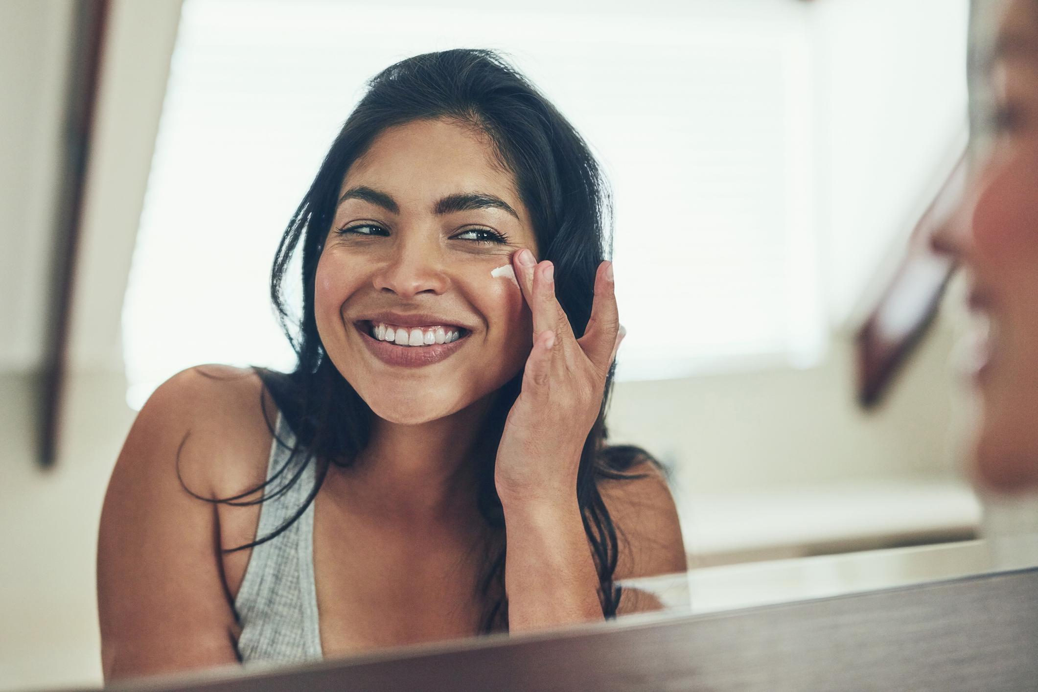 Plan d'une jeune femme qui applique une crème hydratante sur son visage à la maison.