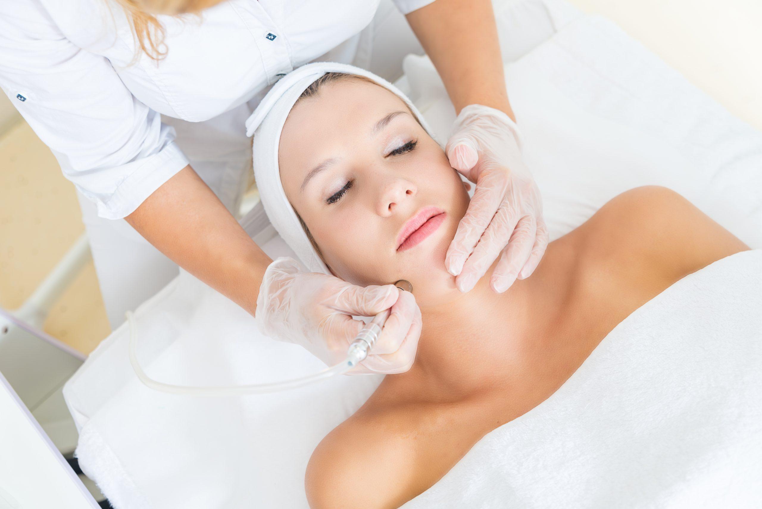 Une femme montre comment se débarrasser des cicatrices d'acné avec la microdermabrasion.