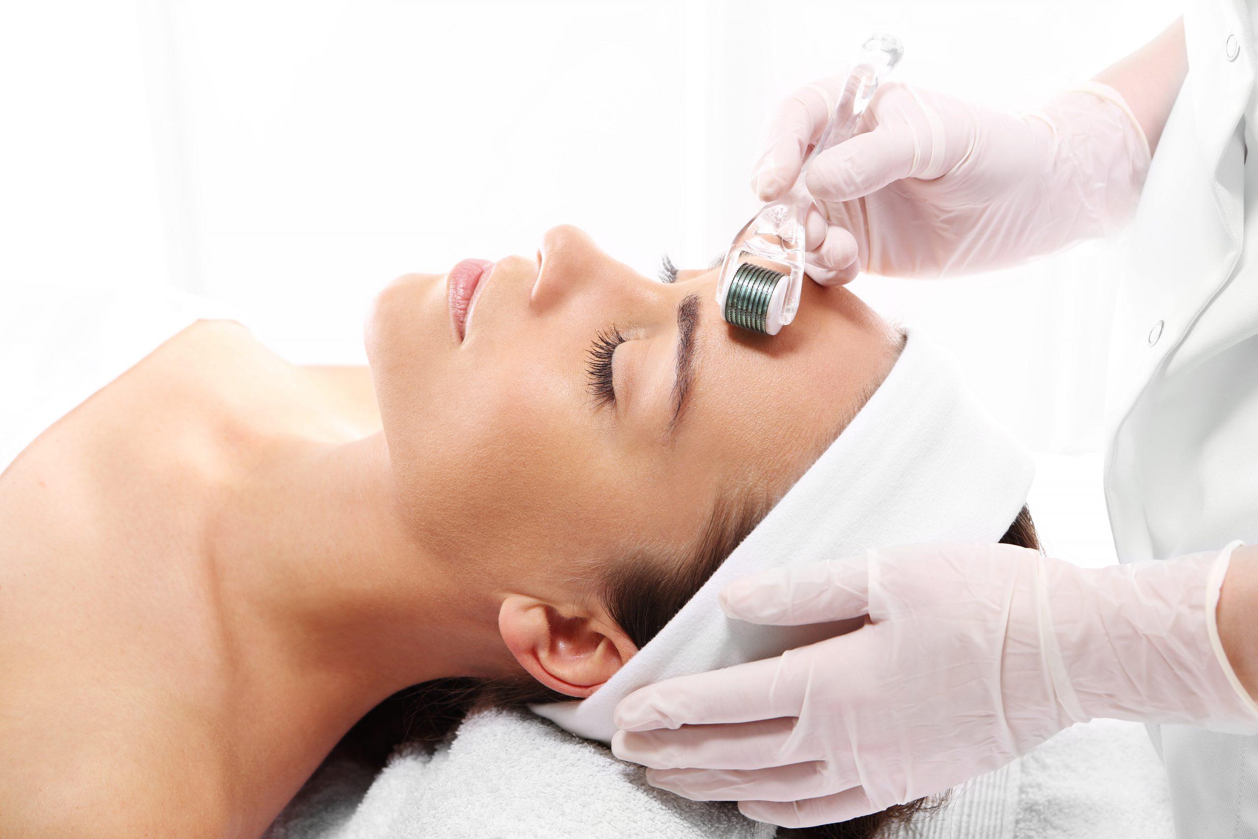 Une femme montre comment se débarrasser des cicatrices d'acné avec le microneedling.