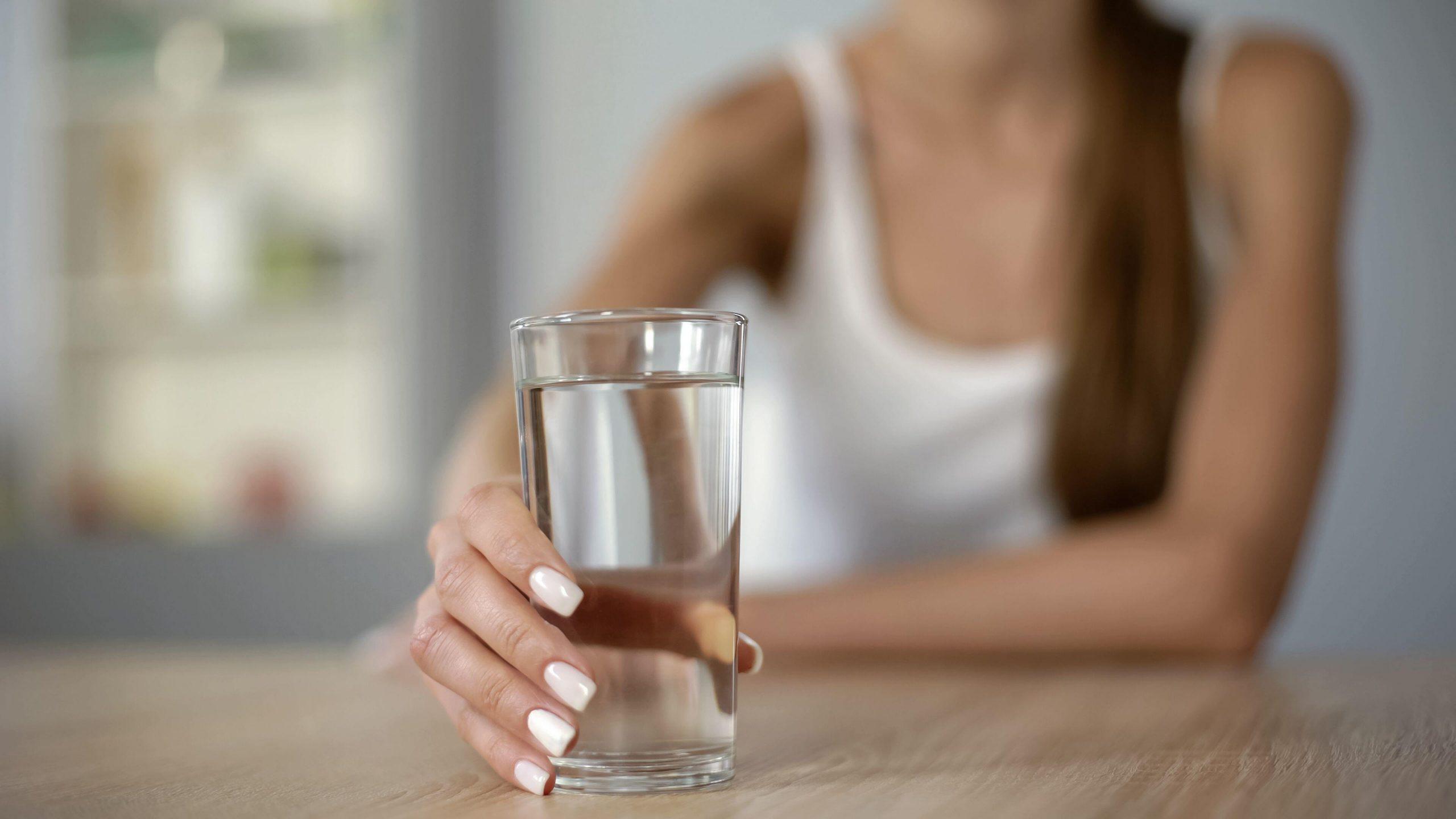 Une femme qui boit de l'eau pour réduire les effets de l'alcool