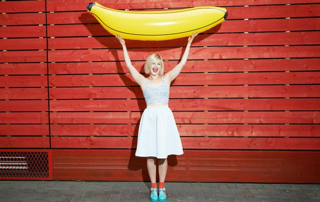 Femme tenant une banane gonflable