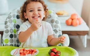 Enfant dans une chaise haute mangeant des fruits