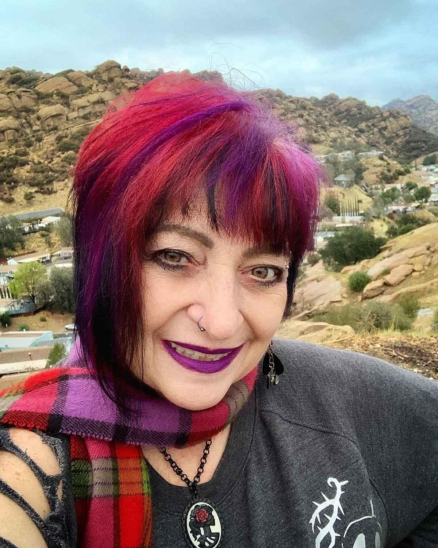 Femme de plus de 60 ans avec une coupe de cheveux rose, violette et rouge très audacieuse et des franges.