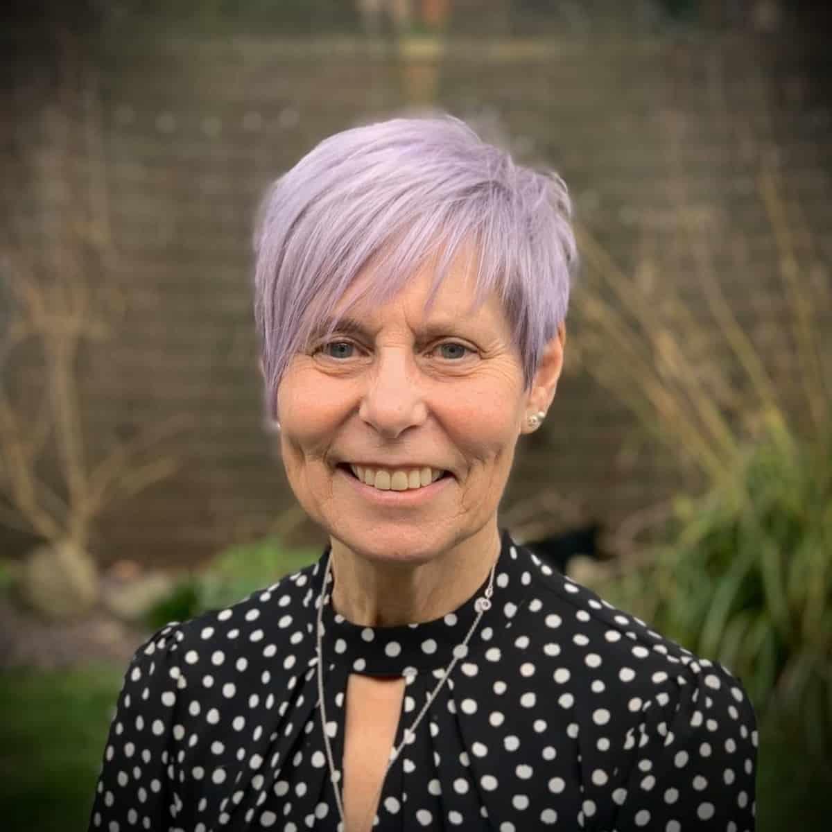 Femme de plus de 60 ans avec une mèche violette et une frange.