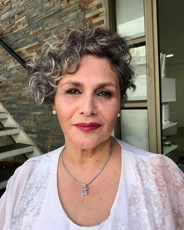 Bob asymétrique bouclé pour une femme de soixante ans aux cheveux courts.
