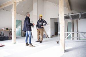 Deux hommes discutent de l'heure à laquelle les constructeurs peuvent commencer à travailler le matin pendant un projet de construction de maison.