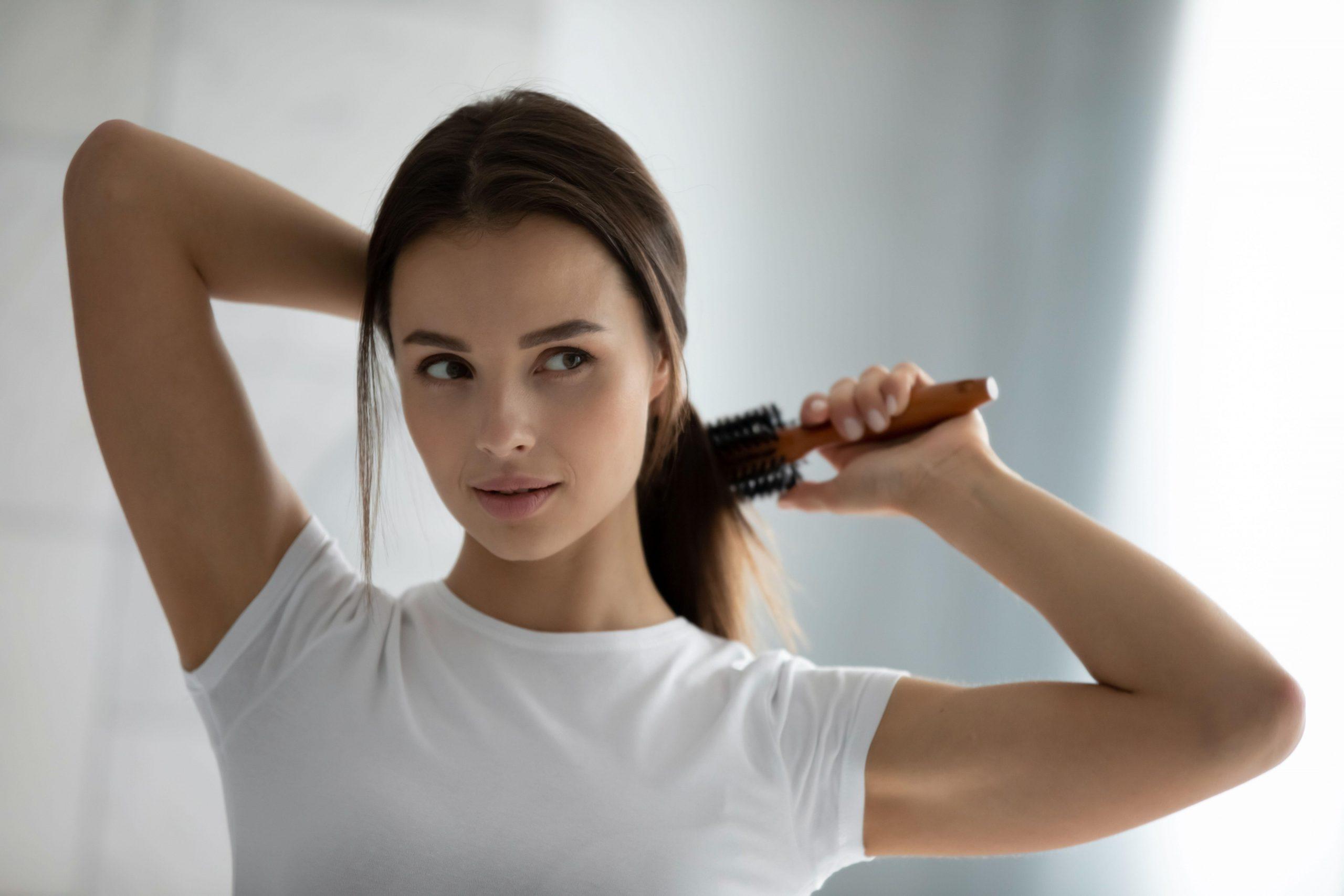 Jeune femme se brossant les cheveux dans la salle de bain avant de se laver