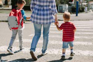 Vue arrière d'une mère raccompagnant ses deux enfants à l'école.