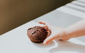 Un enfant cherche un muffin qui pourrait lui faire dépasser l'apport journalier en sucre pour les enfants.